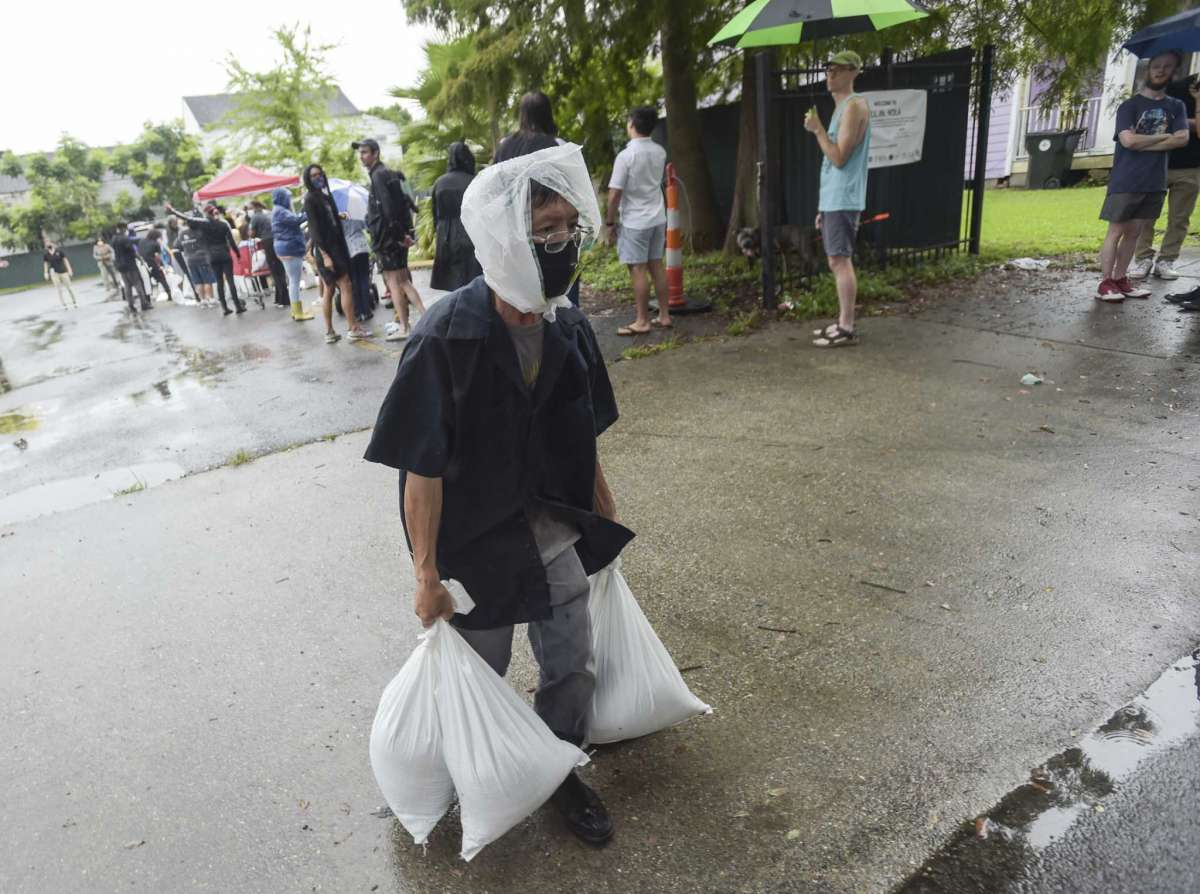 A resident takes home sandbags from a city run sandbag distribution location at the Dryades YMCA along Oretha Castle Haley Blvd., Friday, Aug. 27, 2021, in New Orleans, as residents prepare for Hurricane Ida. (Max Becherer/The Times-Picayune/The New Orleans Advocate via AP)