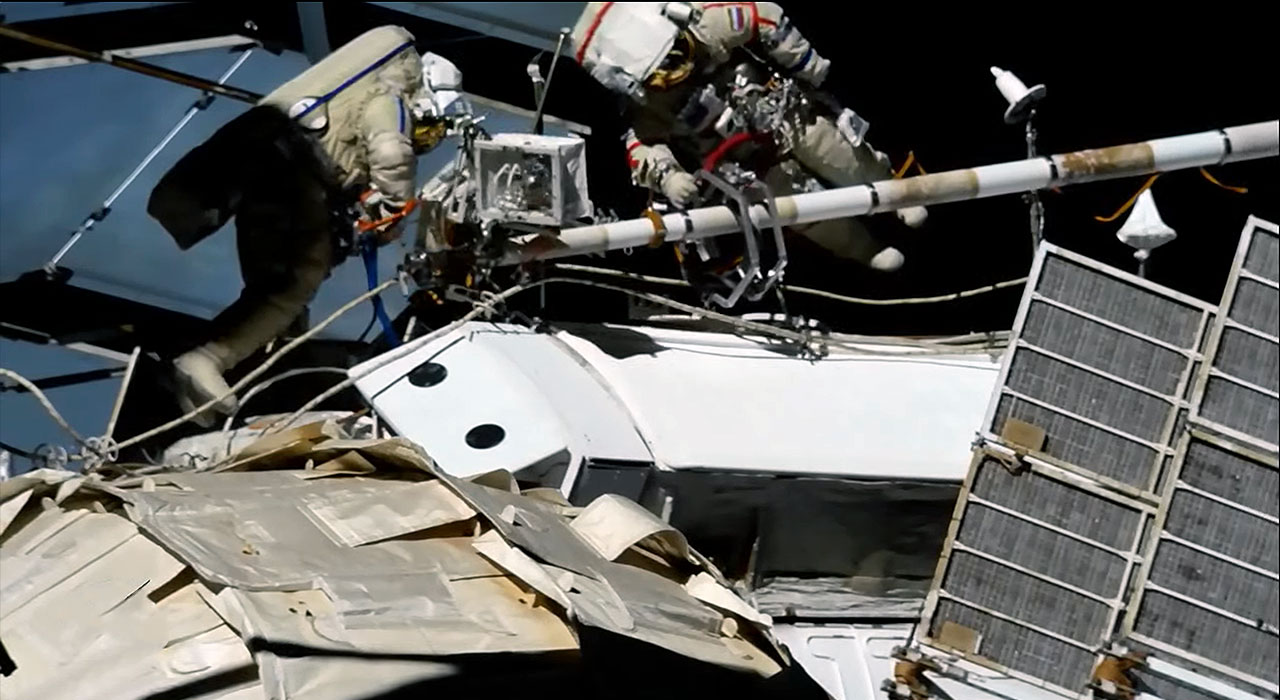 Cosmonauts on spacewalk run power and data to new space station module